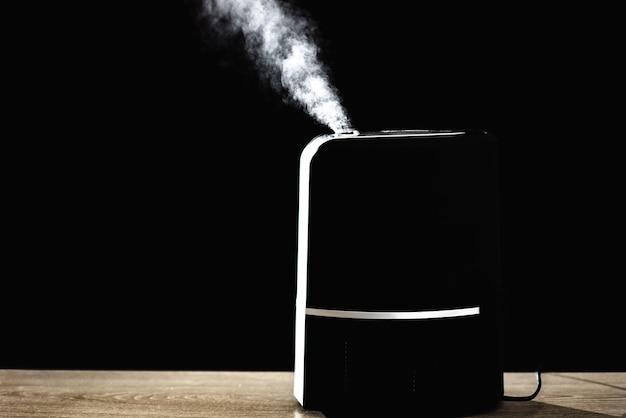 Zwarte luchtbevochtiger op zwarte achtergrond met witte stoom