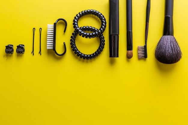 Zwarte make-upborstel en cosmetica op gele plat lag