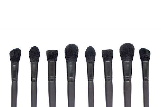 Zwarte make-upborstels die op witte ruimte worden geïsoleerd