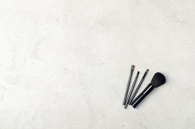 Zwarte make-upborstels op een lichte steenachtergrond