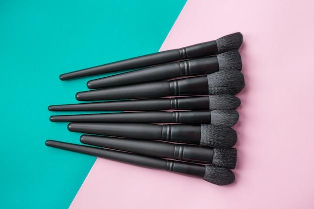 Zwarte make-upborstels op kleurrijke ruimte. bovenaanzicht van make-up borstels set
