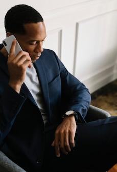 Zwarte man aan de telefoon die naar de tijd kijkt