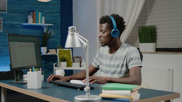 Zwarte man aan het werk als ingenieur met architecturale software op de computer