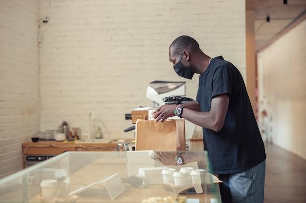 Zwarte man checkt dozen van klanten in pandemie