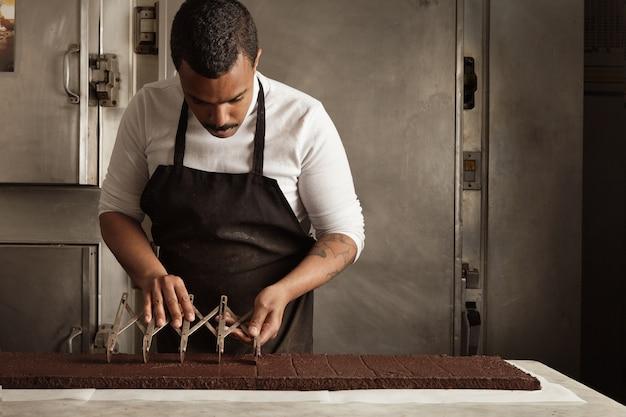 Zwarte man chef gebruikt professionele vintage scheider om chocoladetaart op gelijke porties te splitsen voordat ze worden verpakt, ambachtelijk kookproces