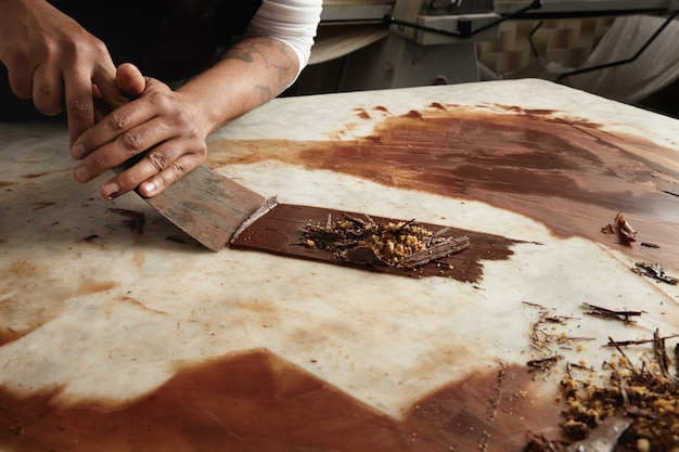 Zwarte man chief verzamelt afgekoelde gesmolten chocolade van marmeren tafel, close-up abstract beeld van werken in chocolade snoepgoed