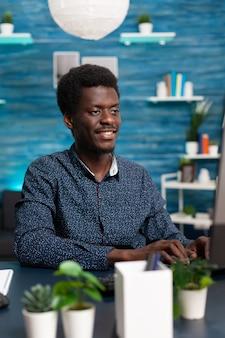Zwarte man computergebruiker werkt vanuit huis aan een gezellig bureau