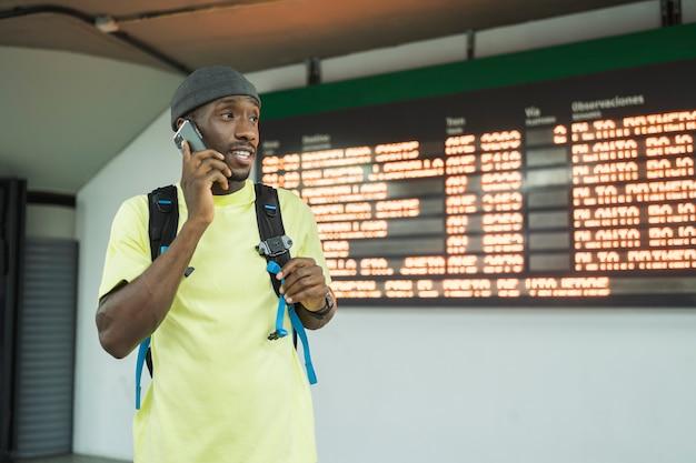 Zwarte man die een gesprek op smartphone maakt. hij kijkt weg. hij draagt een geel t-shirt en een zwarte rugzak. hij tegen het tijdsbord