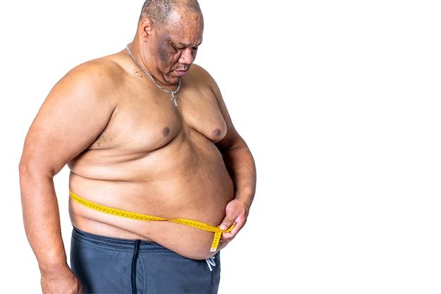 Zwarte man die zwaarlijvig en dik is meet zijn taille met een meetlint of meter om erachter te komen of hij gewicht heeft verloren tijdens een dieet om gewicht te verliezen