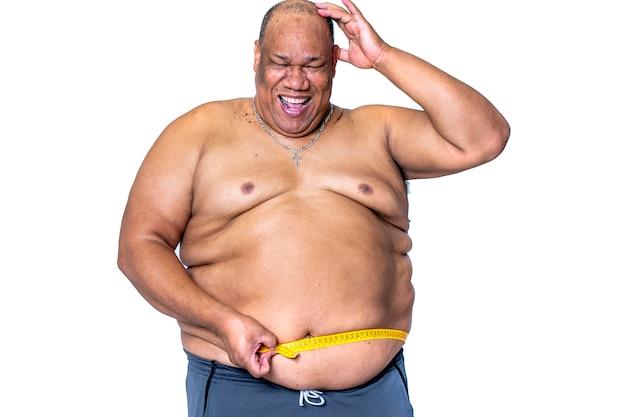 Zwarte man die zwaarlijvig is en een dieet volgt, meet zijn taille met een meetlint dat blij en glimlachend is omdat hij is afgevallen