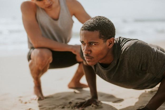 Zwarte man doet push-ups met een trainer op het strand