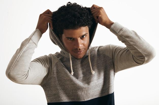 Zwarte man draagt een hoodie op zijn hoofd met krullend haar, op wonderbaarlijke wijze op zoek, geïsoleerd op wit