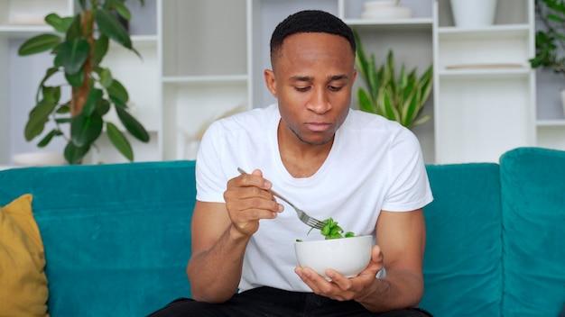 Zwarte man eet gezonde salade binnen zittend op de bank gezond eten concept