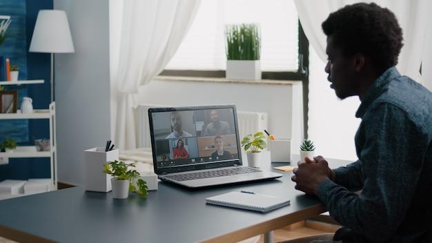 Zwarte man externe werknemer die vanuit huis werkt, online kantooroproep neemt met partners en collega's en hen begroet. computergebruiker vanuit thuiskantoor op video-internetconferentie via webcamconferentiegesprek