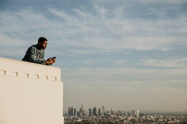 Zwarte man geniet van het uitzicht op de stad los angeles vanaf het griffith observatory, vs