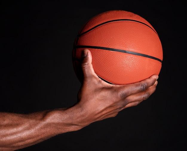 Zwarte man hand houdt basketbal bal