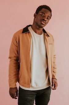 Zwarte man in bruin jasje op roze achtergrond studioschot