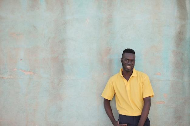 Zwarte man in een geel overhemd lachend achter de muur