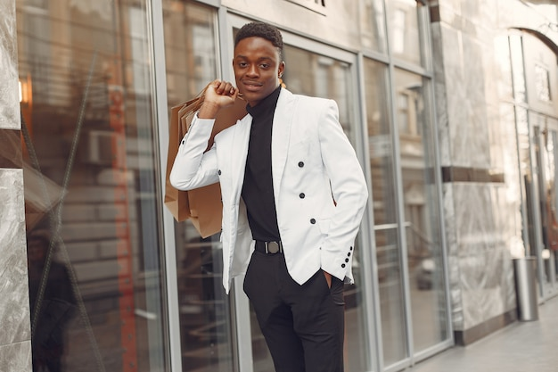 Zwarte man in een witte jas met boodschappentassen