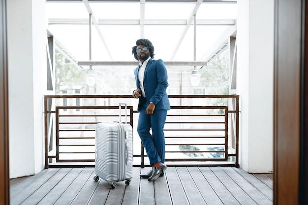 Zwarte man in formeel pak met ingepakte koffer hoteldeur binnen