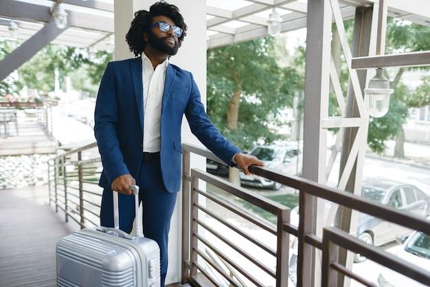 Zwarte man in formeel pak met ingepakte koffer hoteldeur binnen.