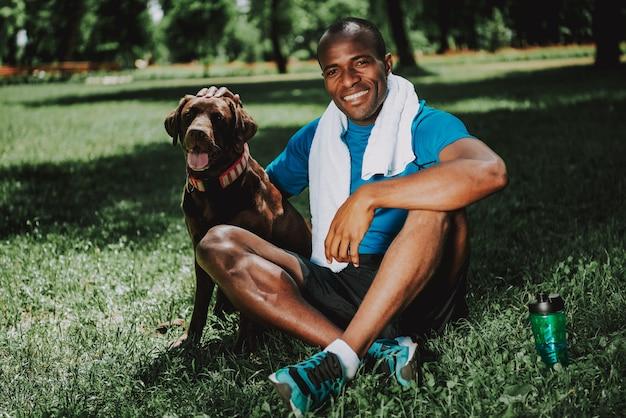 Zwarte man in sportkleding zittend op gras met bruine hondje.