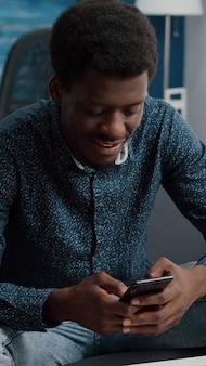 Zwarte man in zijn woonkamer die telefoon gebruikt om door sociale media te bladeren