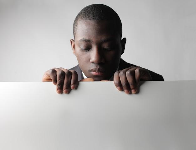 Zwarte man kijkt neer op een bord