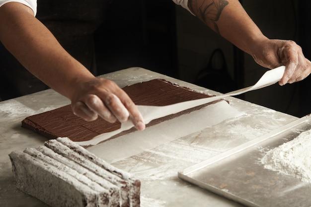 Zwarte man kookt chocoladetaarten in zijn professionele ambachtelijke banketbakkerij.
