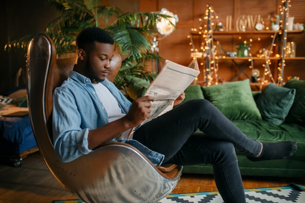 Zwarte man krant lezen in een comfortabele lederen stoel in de woonkamer, ontspanning thuis.