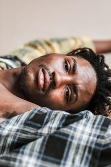 Zwarte man liggend op een geruit t-shirt