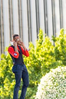 Zwarte man luisteren naar muziek een mobiele telefoon