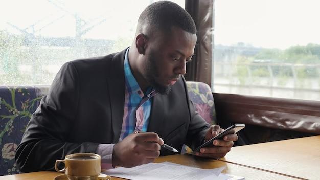 Zwarte man maakt papierwerk. afro-amerikaanse zakenman vult documenten in zomertentcafé op zoek in smartphone. papieren schrijven. warme kop koffie op tafel. hij draagt hemd en colbert.