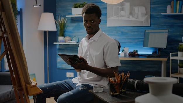 Zwarte man met artistieke vaardigheden die tablet gebruikt voor vaasontwerp