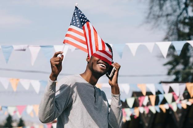 Zwarte man met de vlag van de vs en smartphone