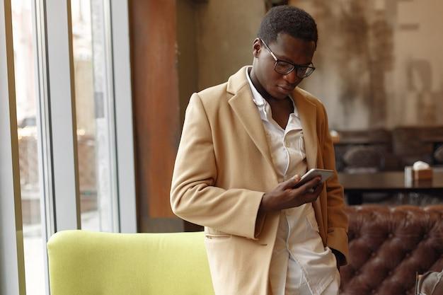 Zwarte man met een bruine jas staande met mobiele telefoon