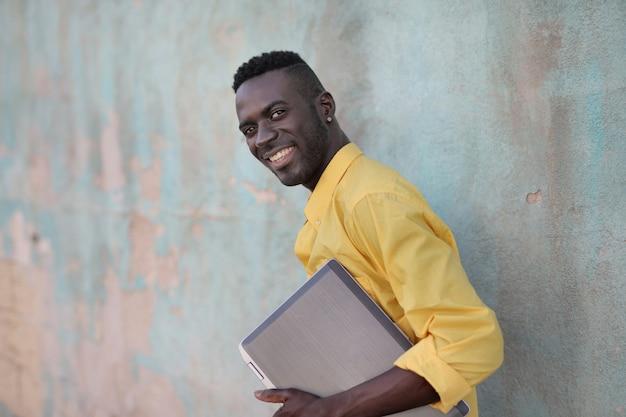 Zwarte man met een koffer in zijn handen lachend achter een muur
