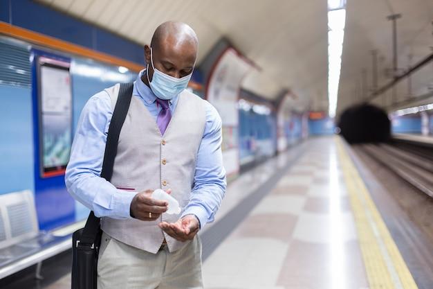 Zwarte man met gezichtsmasker ontsmettingsgel op zijn handen te zetten.