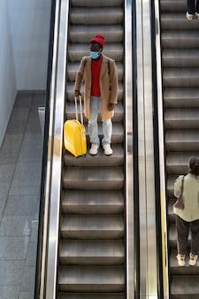 Zwarte man met koffer staat op roltrap in luchthaven draagt gezichtsmasker tijdens covid-19 pandemie.