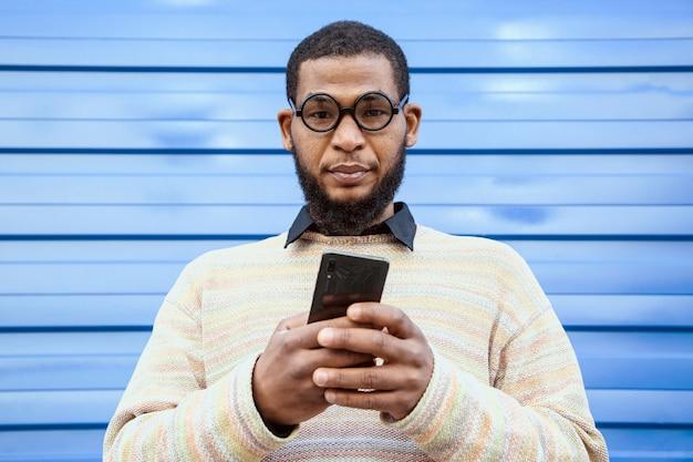 Zwarte man met ronde nerd bril, kijkend naar de camera. een blauwe straatmuur op de achtergrond.