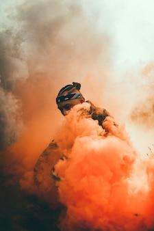 Zwarte man omringd door oranje rook