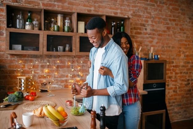 Zwarte man ontbijt koken in de keuken. afrikaans paar dat groentesalade thuis voorbereidt. gezonde vegetarische levensstijl