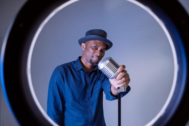 Zwarte man op het punt om een vintage lied te zingen. geïsoleerde man zingen etnische culturele liedjes.