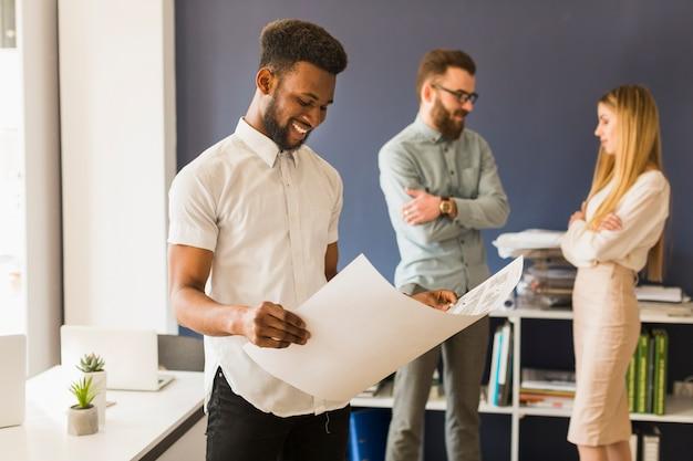 Zwarte man op zoek naar ontwerp op kantoor