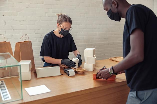 Zwarte man schrijft datum van bezoekers in notitieboekje
