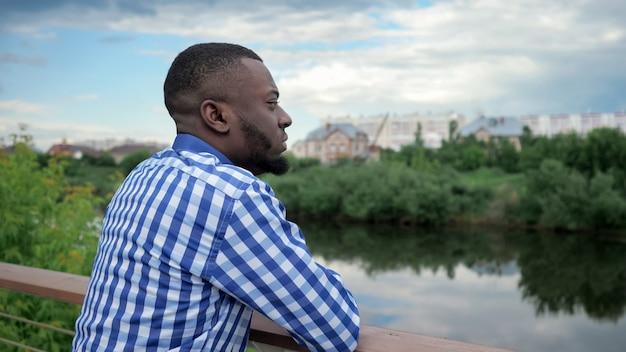 Zwarte man staat aan de waterkant van de stad in de buurt van het hek in het park en bewondert het uitzicht op de stad.