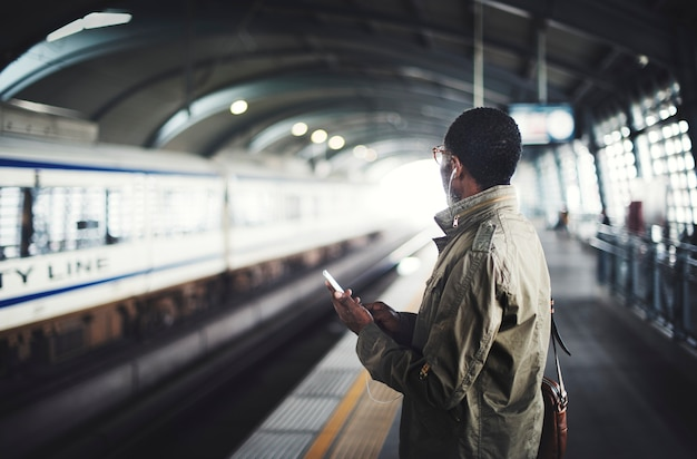 Zwarte man te wachten voor een trein op het platform