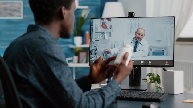 Zwarte man thuis op zoek naar medische hulp van arts via online internet-telegezondheidsoverleg met huisarts. gezondheidscontrole via virtuele videoconferentie, patiënt op zoek naar medicijnadvies