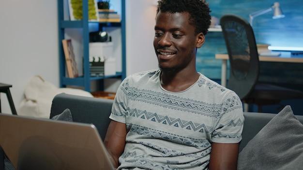 Zwarte man werkt vanuit huis voor zakelijk project op laptop