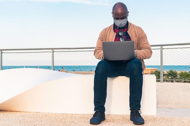 Zwarte man whit het gezichtsmasker, werk op laptop zittend op een bankje in het park - afro-amerikaanse zakenman kijken laptop scherm praten met vriend informeel videogesprek